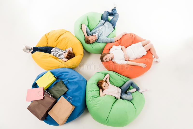 High angle view of family with two children. Resting on bean bag chairs after shopping stock photo