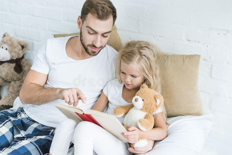 High angle view of father and adorable little daughter reading book together royalty free stock photos