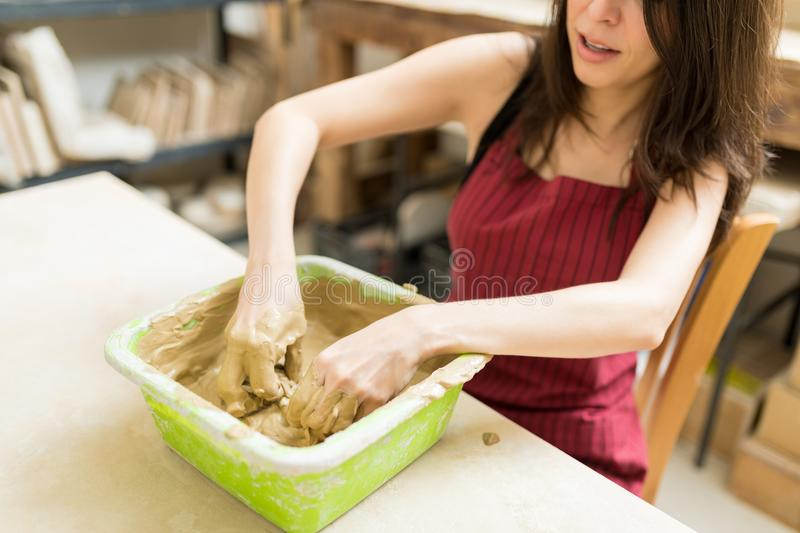 Entrepreneur Mixing Clay In Container At Pottery Workshop stock image