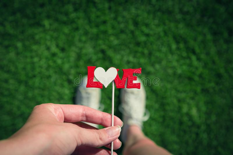 Close up of female holding stick with love sign and standing on. High angle view of female hand holding love sign on stick against green grass background royalty free stock photos