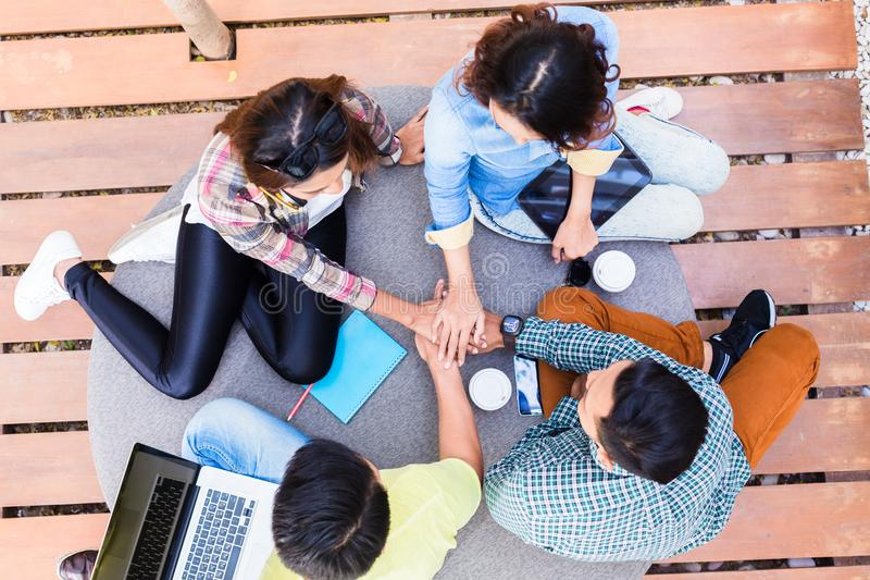 Young employees using modern wireless technology while working o. High angle view of four young employees using modern wireless technology while working outdoors royalty free stock photo