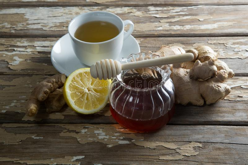 High angle view of fresh honey and lemon with ginger tea on table royalty free stock photo