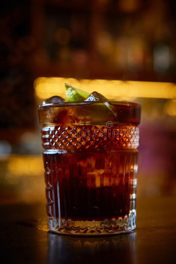 High angle view of a glass of Cuba Libre cocktail with rum, coke, lemon juice and ice cubes stock image