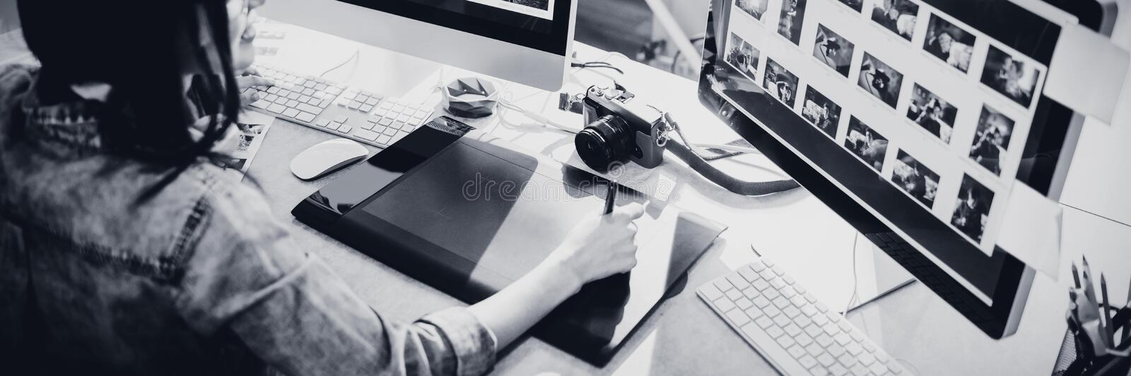 High angle view of graphic designer using graphics tablet. High angle view of female graphic designer using tablet while working on computer at office royalty free stock image