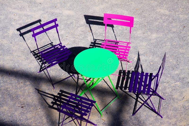 High angle view on green round table with four wood pink and purple folding chairs outdoor in bright sunlight royalty free stock image