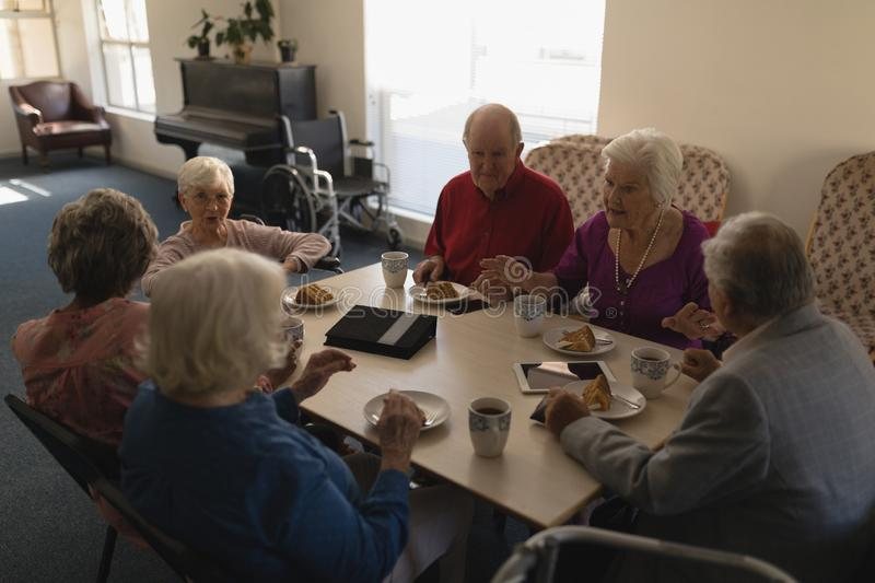 High angle view of group of senior friends having breakfast on dining table stock photo