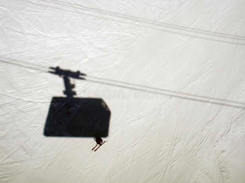 A high angle view of a guy skiing and a shadow of ski lift in the alps switzerland.  stock photos
