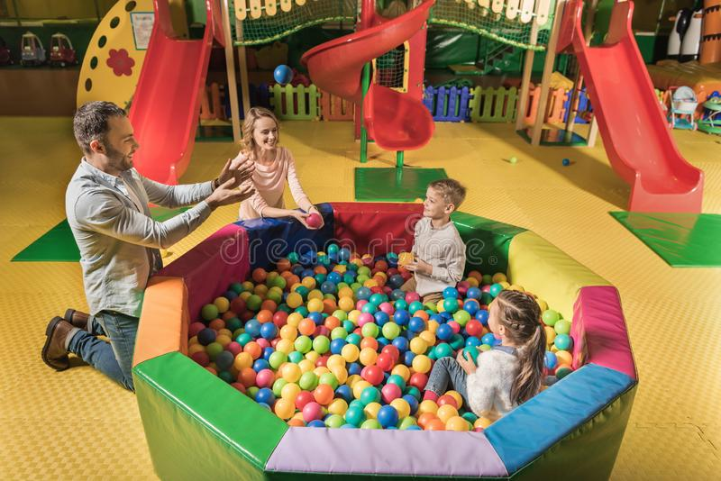 high angle view of happy family with two adorable kids playing with colorful balls in entertainment royalty free stock image