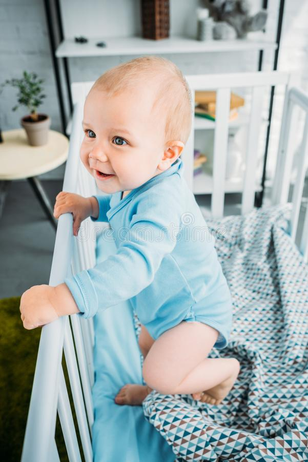 High angle view of happy little baby standing. In crib royalty free stock photography