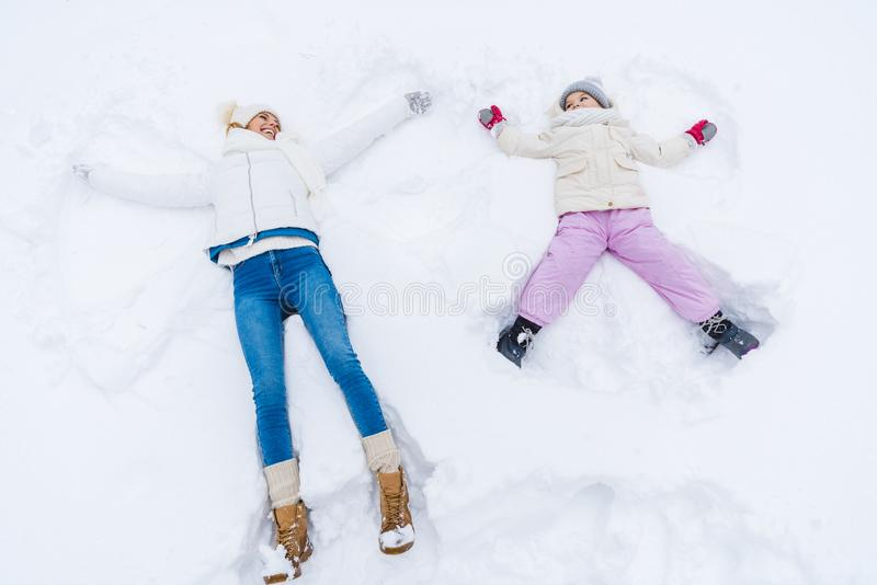 high angle view of happy mother and daughter making snow angels and smiling royalty free stock image
