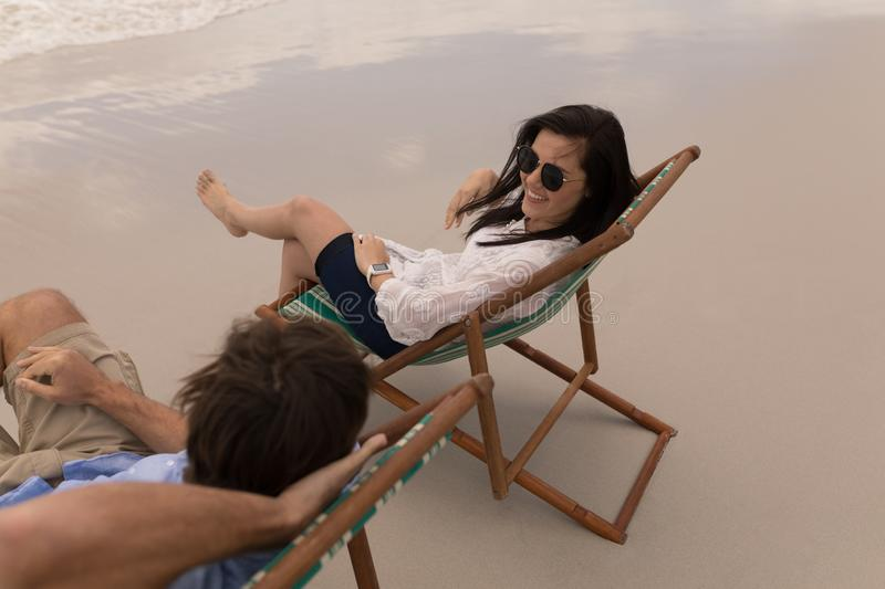 Young couple relaxing on sun lounger and talking with each other royalty free stock images