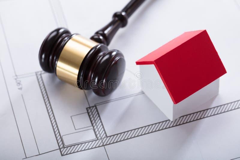 House Model And Gavel On Blueprint. High Angle View Of House Model With Red Roof And Gavel On Blueprint stock photos