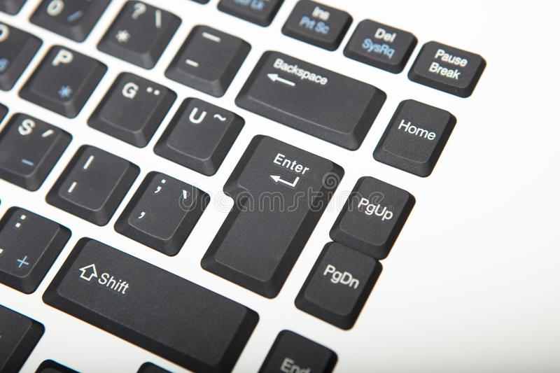 High angle view of a keyboard keys close-up. High angle view of a computer keyboard with selective focus to the Enter key and copy space to the right stock image