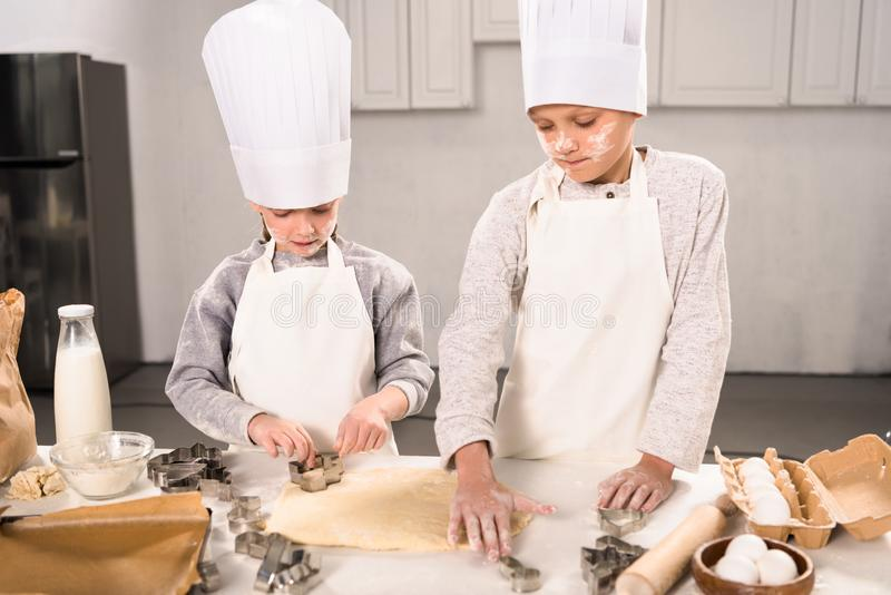 High angle view of kids in chef hats and aprons cutting out dough for cookies at table. In kitchen stock photography