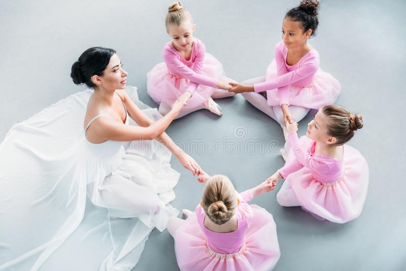 high angle view of little ballerinas and ballet teacher exercising together stock photo