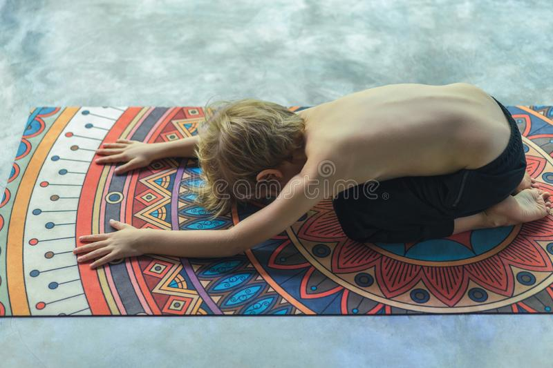 High angle view of little kid practicing yoga in Extended Child. (Utthita Balasana) pose stock photos