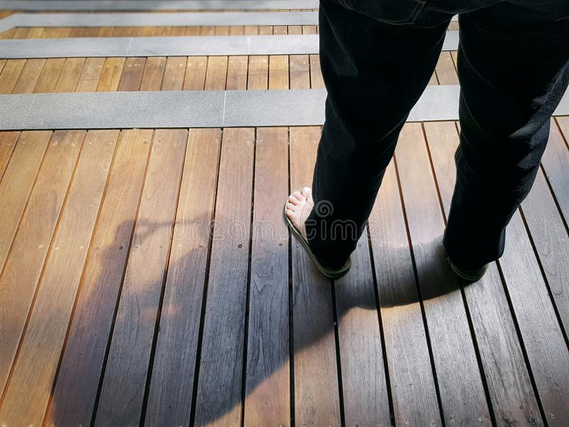 Low Section of a Woman Wearing Jeans Standing on Wooden Plank Stairs. High Angle View of Low Section of a Woman Wearing Jeans Standing on Wooden Plank Stairs royalty free stock photography