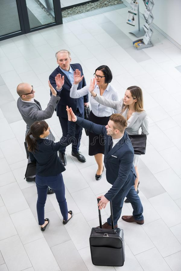 Business Colleagues Giving Highfive While Standing In Office Lob stock photo
