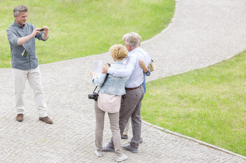 High angle view of man photographing friends at park royalty free stock photography