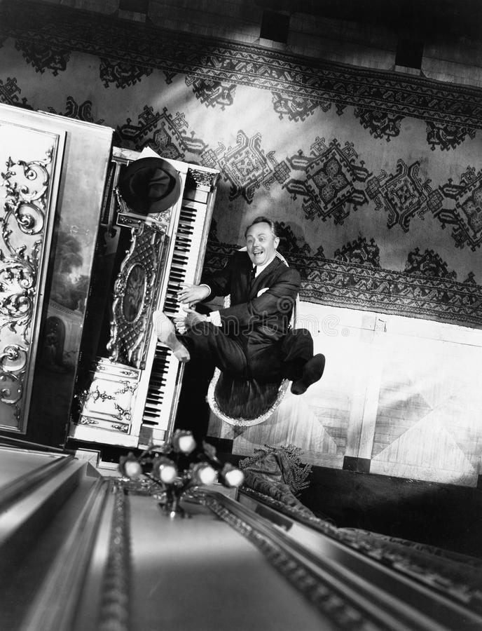 High angle view of a man reclining on a chair and playing a piano. (All persons depicted are no longer living and no estate exists. Supplier grants that there stock photo