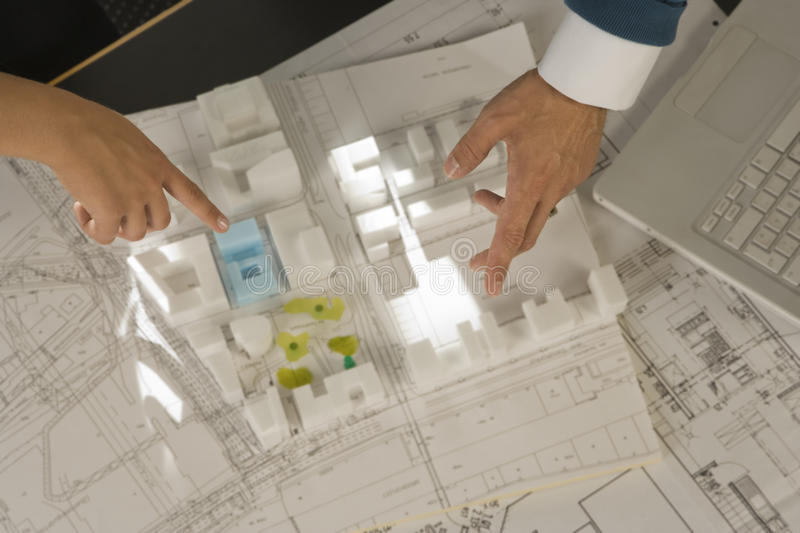 High angle view of a man and a woman`s hands pointing at an architectural model stock image