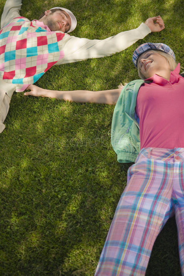 High angle view of a mid adult couple lying on grass stock photos