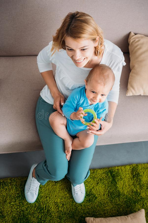 High angle view of mother holding her adorable child. On knees while sitting on couch stock images