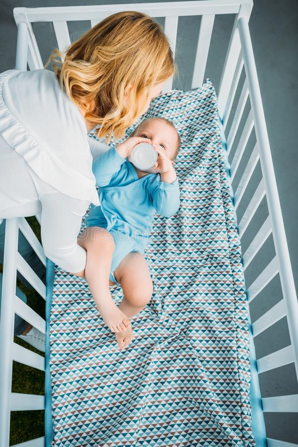 High angle view of mother putting her little child. Into crib at home stock image