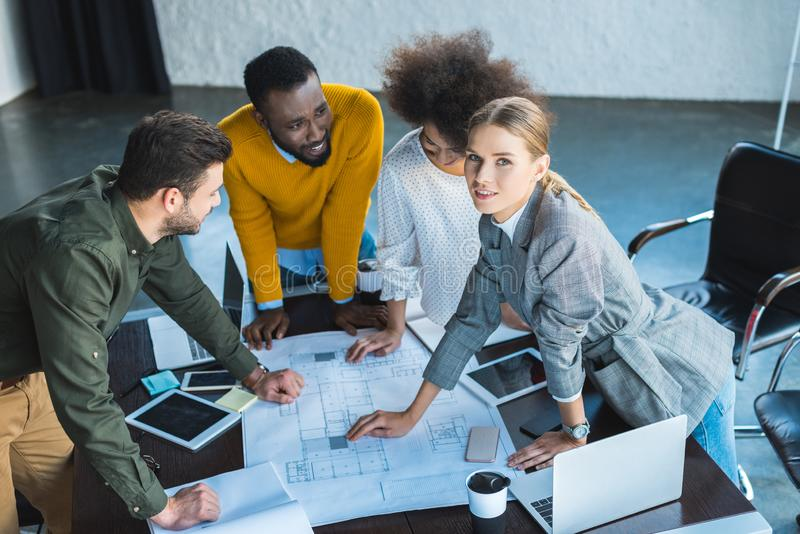 high angle view of multicultural businesspeople working with blueprint royalty free stock image