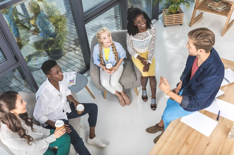 high angle view of multiethnic business coworkers resting during coffee break royalty free stock photo