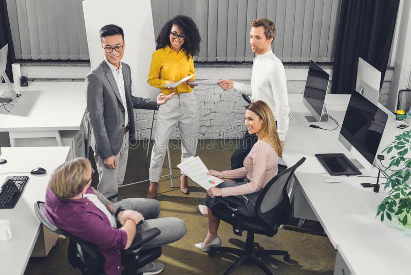High angle view of multiethnic young businesspeople working together royalty free stock photography
