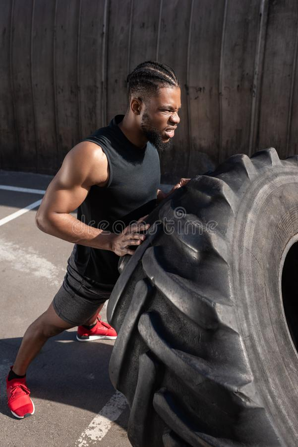 High angle view of muscular african american man. Exercising with tyre on street stock photography