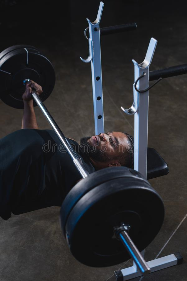 High angle view of muscular african american man. Lifting barbell in gym royalty free stock photos