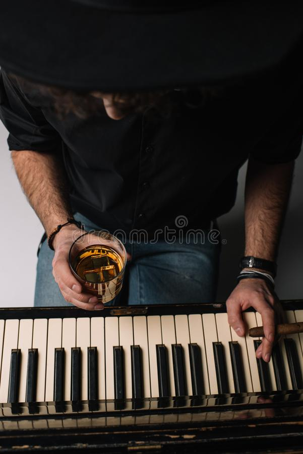 High angle view of musician with glass of whiskey and cigar. Playing piano royalty free stock photos