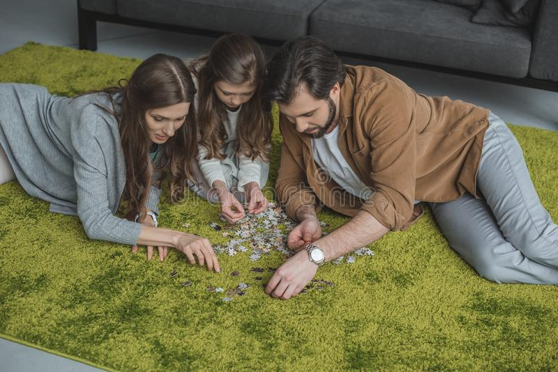 high angle view of parents and daughter connecting puzzle pieces on carpet stock photography