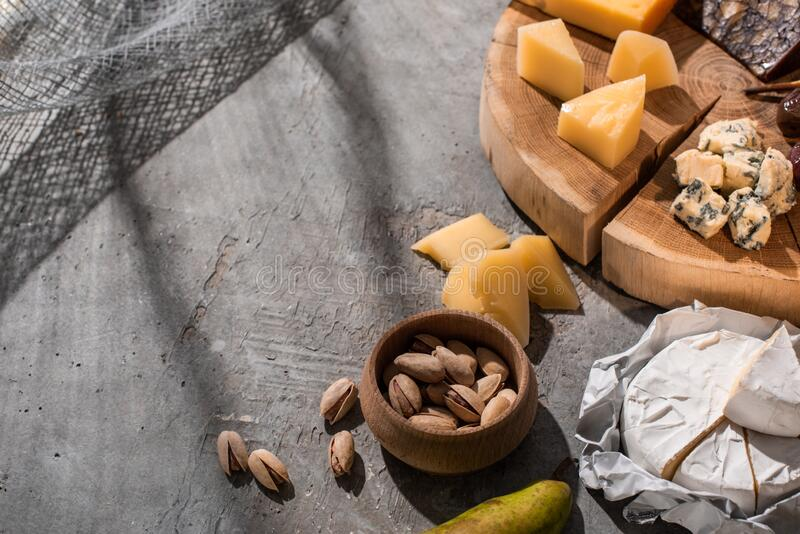 High angle view of pear, pistachios and camembert next to different kinds of cheese on wooden board on grey background. High angle view of pear, pistachios and royalty free stock photo