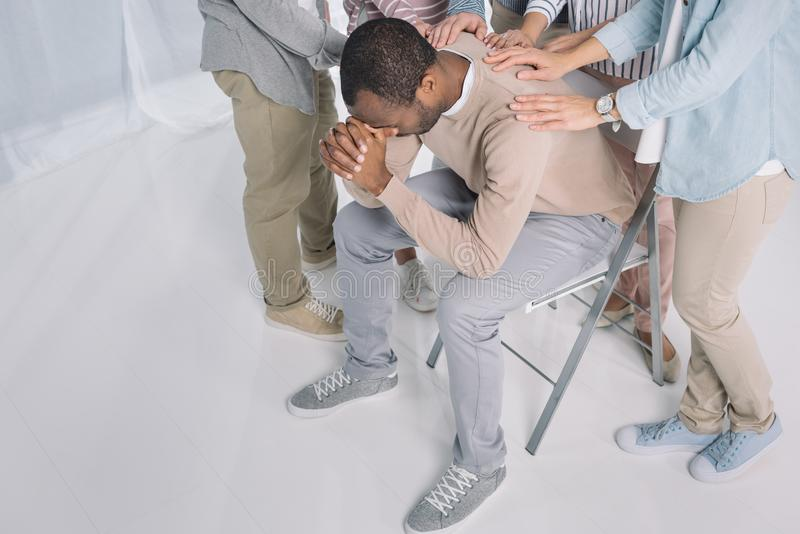 high angle view of people supporting depressed african american man royalty free stock image