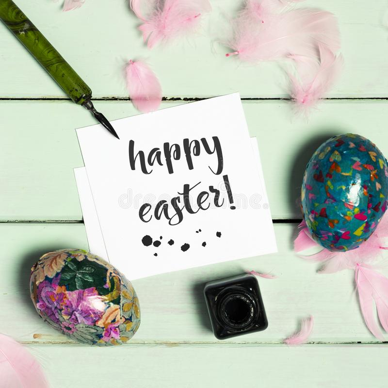 Homemade easter eggs and text happy easter. High angle view of a piece of paper with the text happy easter written in it, an ink bottle, a dip pen, some stock photography