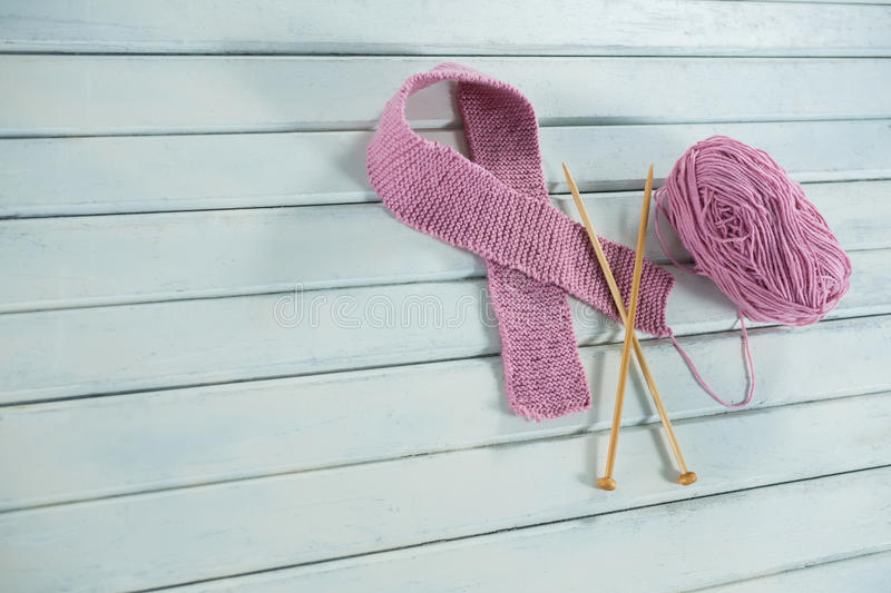 High angle view of pink woolen Breast Cancer Awareness ribbon with crochet needles by yarn royalty free stock image