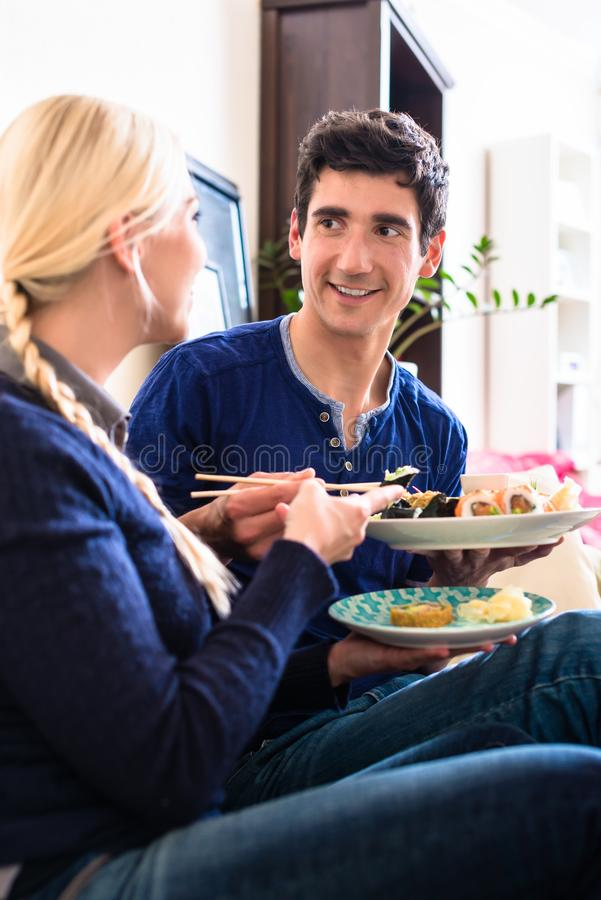 Portrait of happy young couple eating traditional Asian food. High angle view portrait of happy young couple looking at camera while eating traditional Asian royalty free stock images