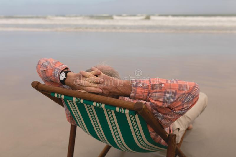 Senior man relaxing with hands behind head in a sun lounger on the beach royalty free stock photo