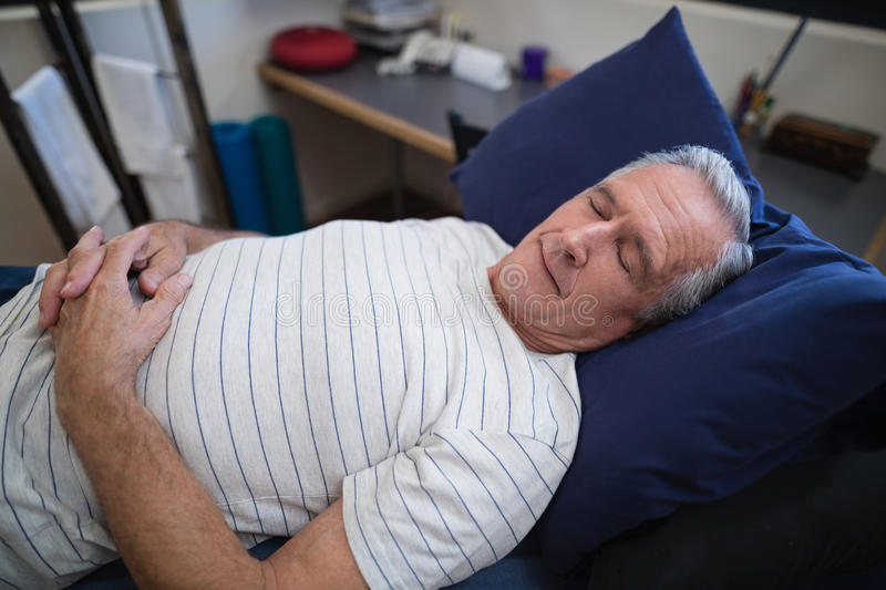 High angle view of senior man sleeping on bed royalty free stock photography