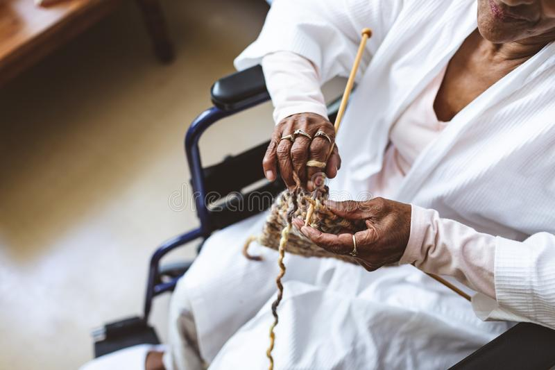 Senior woman sitting and knitting with wool at retirement home stock photos