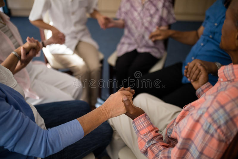 High angle view of seniors and female doctor holding hands while sitting on chairs. At retirement home stock images