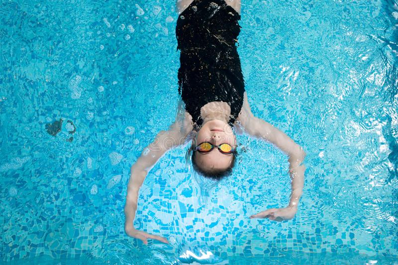 Calm kid enjoying swimming. High angle view of serious calm girl wearing goggles and athletic swimwear floating on water while swimming in pool royalty free stock image