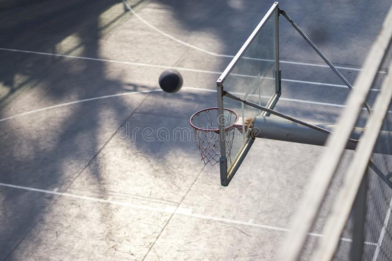 High angle view of shooting basketball in outdoor court nobody. High angle view of basketball in the air toward hoop nobody royalty free stock photos
