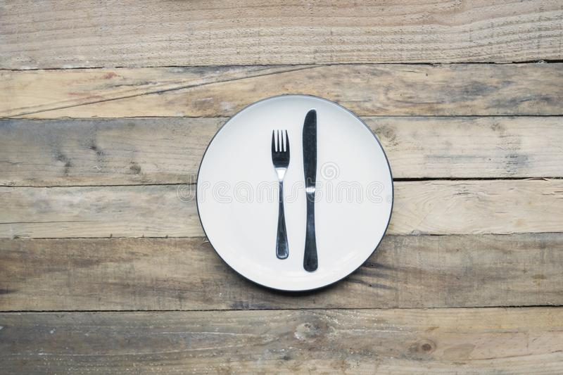 Silver knife and fork on an empty plate royalty free stock image