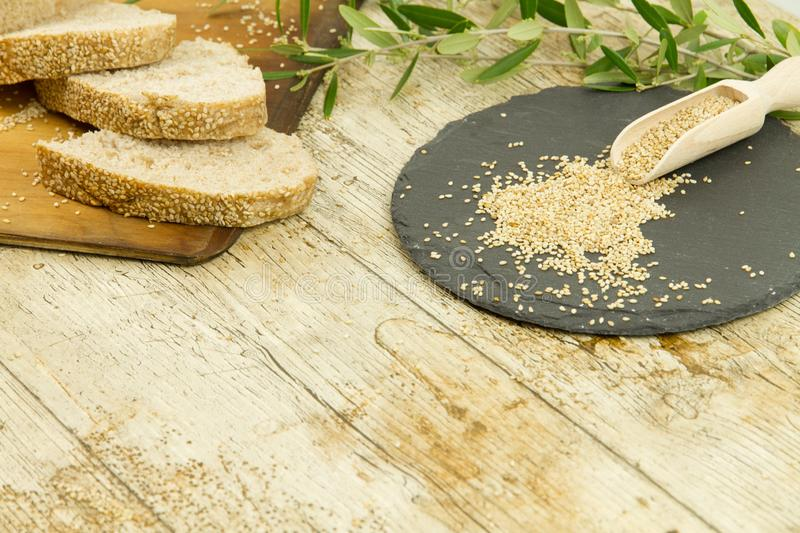 High angle view of a sliced loaf of sesame seeds homemade bread on wooden cutting board, sesame seeds on slate plate and an olive royalty free stock photo