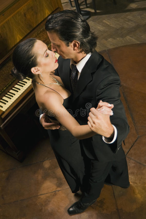High angle view of a smartly dressed young couple dancing. In front of a piano stock photos