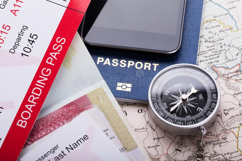 Smartphone, Boarding Pass Ticket, Passport And Compass On Map royalty free stock photo